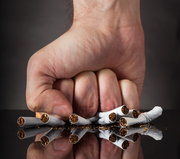 Close-up Of  Man's Fist Crushing Cigarettes Over Black Background