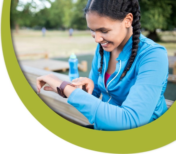 Smiling young sporty woman checking smartwatch in park. She is sitting on bench during daytime. Female is in sportswear. Athlete is representing healthy lifestyle.